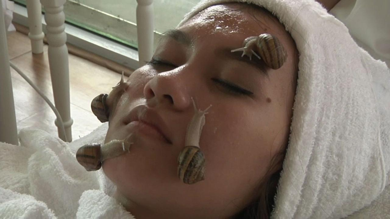 A woman is shown getting a facial treatment with snails.