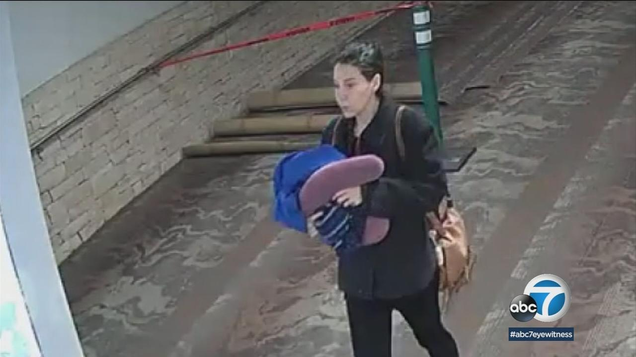 A woman is shown in surveillance video carrying what appears to be something wrapped in a blanket in the Tucson Airport.