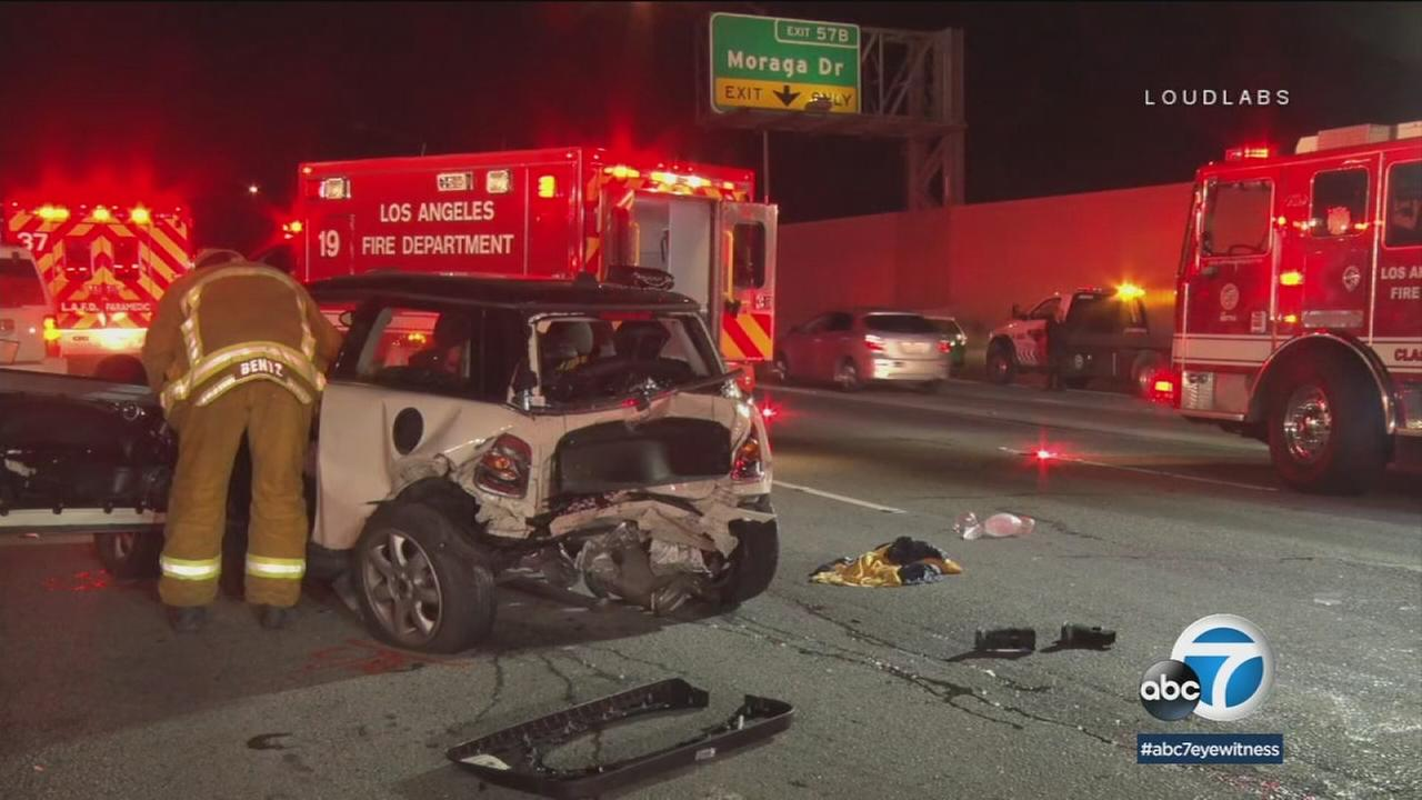 A 29-year-old woman died and two men were hospitalized after a car slammed into another car that was stopped in lanes on the 405 Freeway in Bel Air, authorities said.