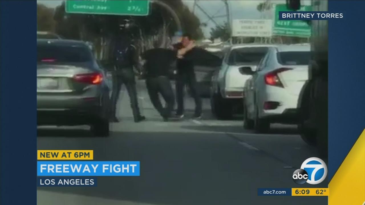Two men are shown fighting in the eastbound lanes of the 105 Freeway in South Los Angeles.