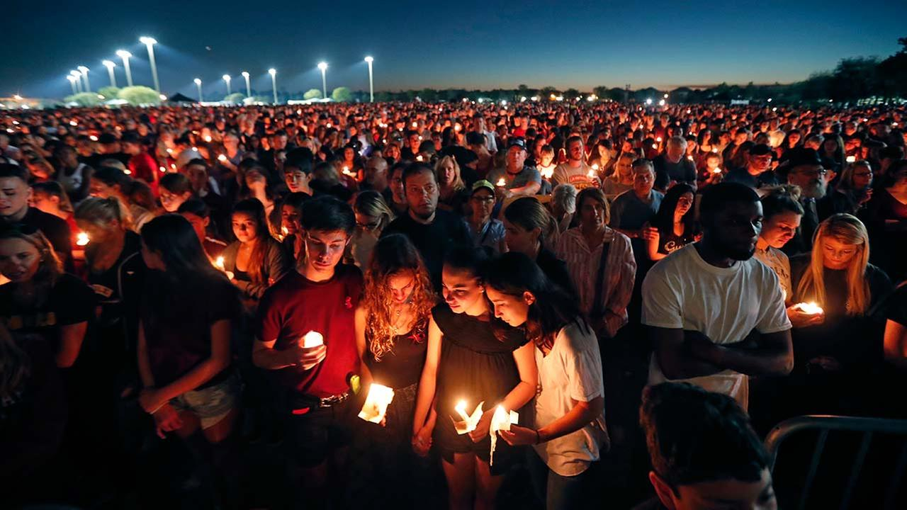 People attend a candlelight vigil for the victims of the Wednesday shooting at Marjory Stoneman Douglas High School, in Parkland, Fla., Thursday, Feb. 15, 2018.