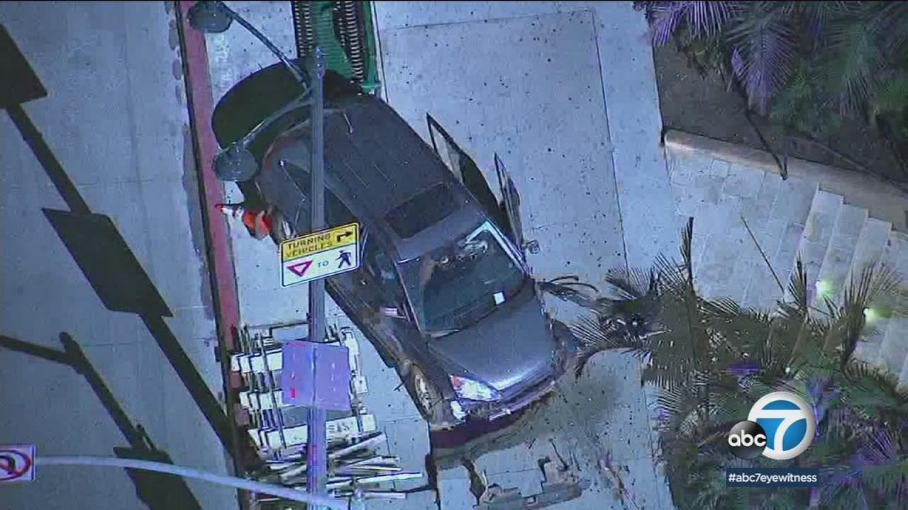 A mangled vehicle is shown on the sidewalk along an intersection in Beverly Hills after a wild chase that ended in a crash.