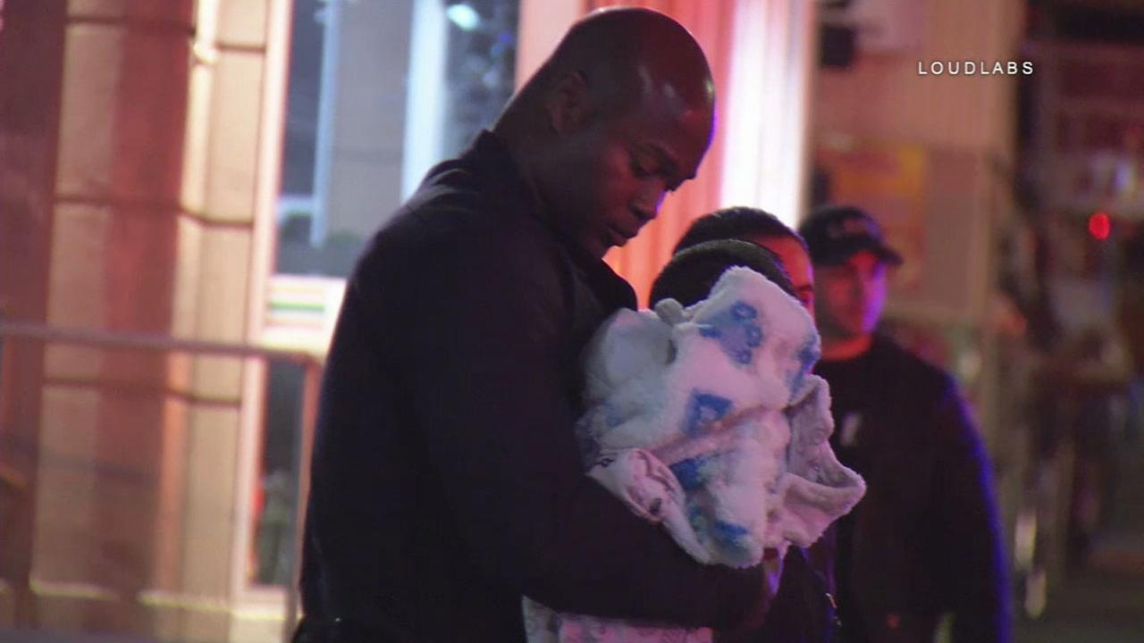 LAPD Officer Alex Frazier holds a 3-week-old infant in his arms after performing CPR and reviving the child of suspected abuse in the Westlake District.