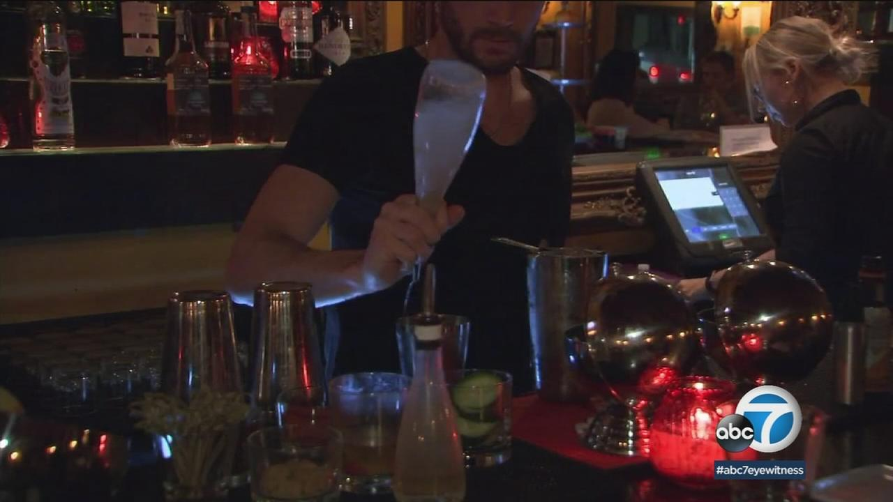 A SoCal bartender is seen pouring a drink at a bar in an undated photo.