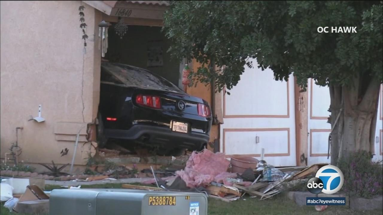 A black Ford Mustang is seen mangled inside a Moreno Valley home after crashing and striking a woman inside on Monday, March 19, 2018.