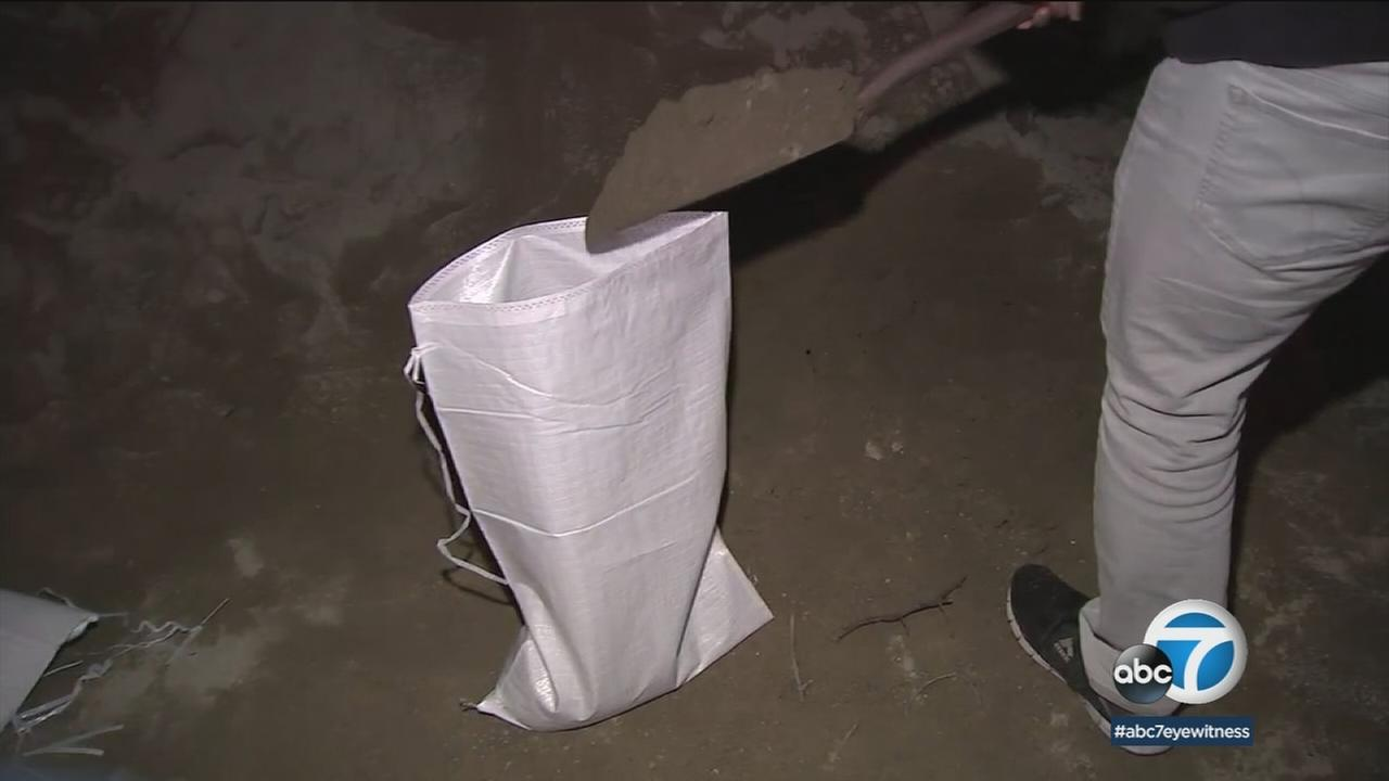 A Los Angeles resident gathers up sand and creates a sandbag to use in front of their home ahead of a major storm headed for Southern California.
