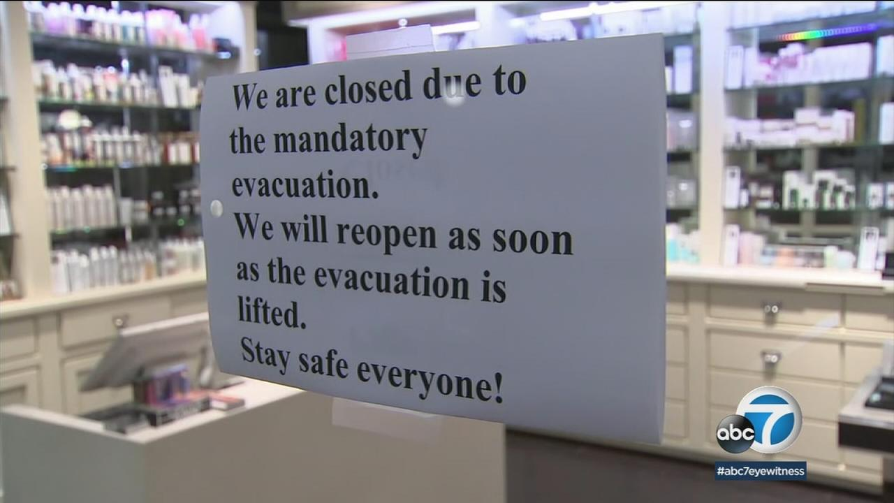 A sign shows the closure of a business due to a mandatory evacuation in Montecito as a powerful storm heads into the area.