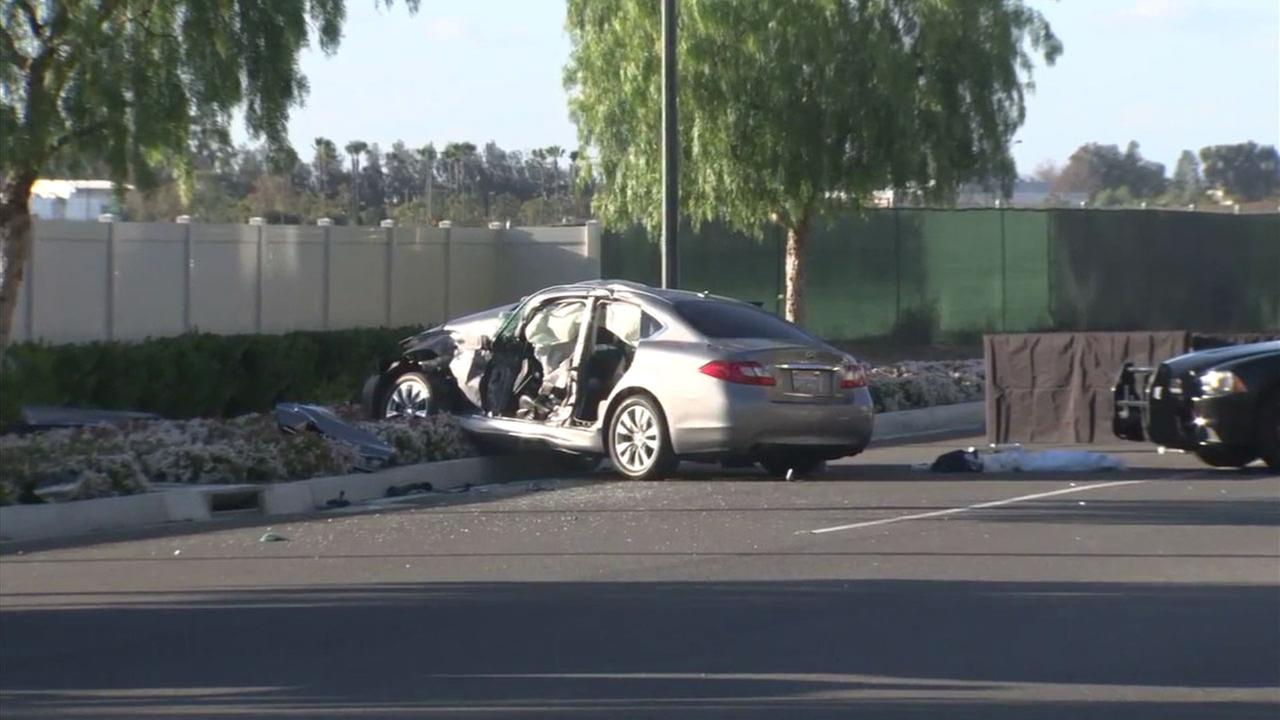 A mangled 2011 gray Infiniti is shown along a roadway in Tustin after a fatal crash.