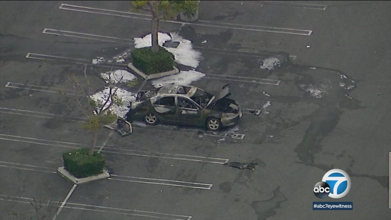 A persons body was found inside a burned-out car after the sedan erupted in flames in the parking lot of a Bell Gardens shopping mall.