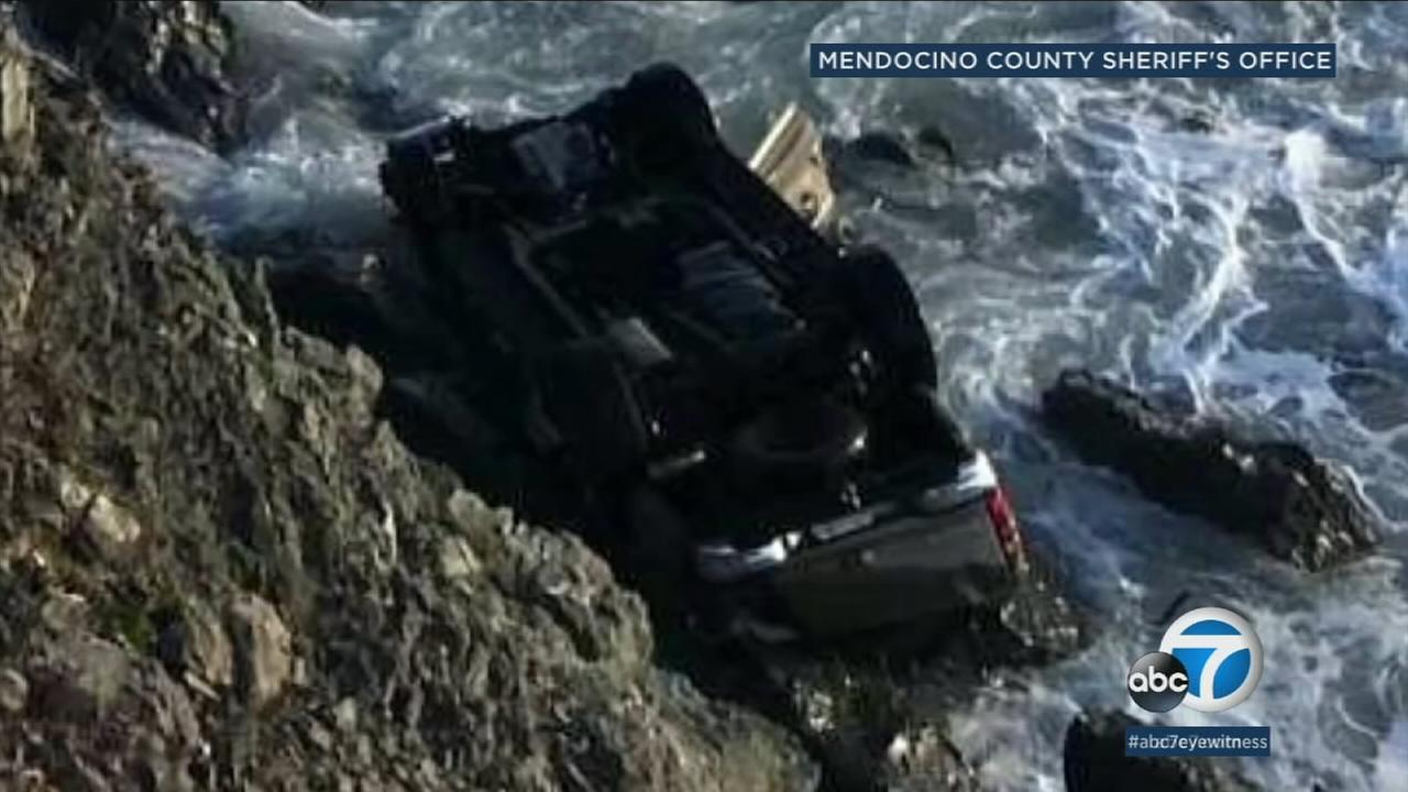 A mangled SUV is shown upside down on rocks off the coast of Medocino, California, where a family of eight went off a cliff.