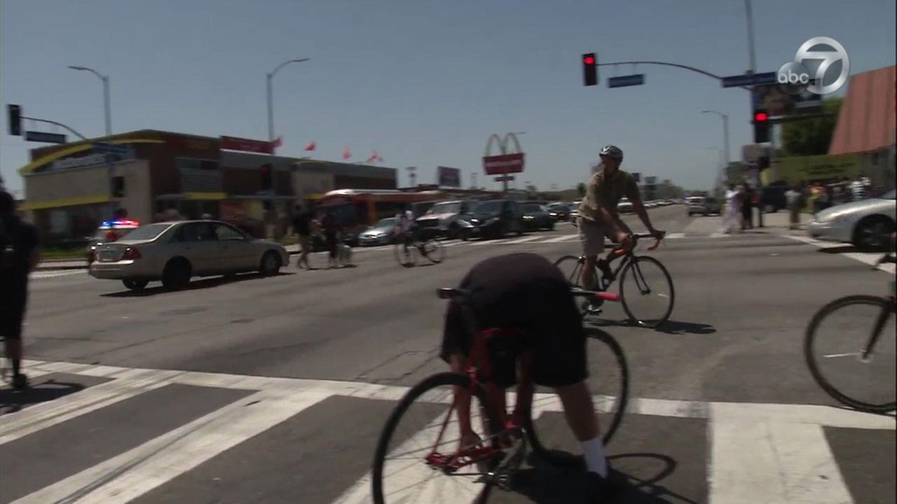 A pedestrian blocking traffic at an intersection to protest hit-and-run crashes is shown about to be struck by a hit-and-run vehicle in South Los Angeles.