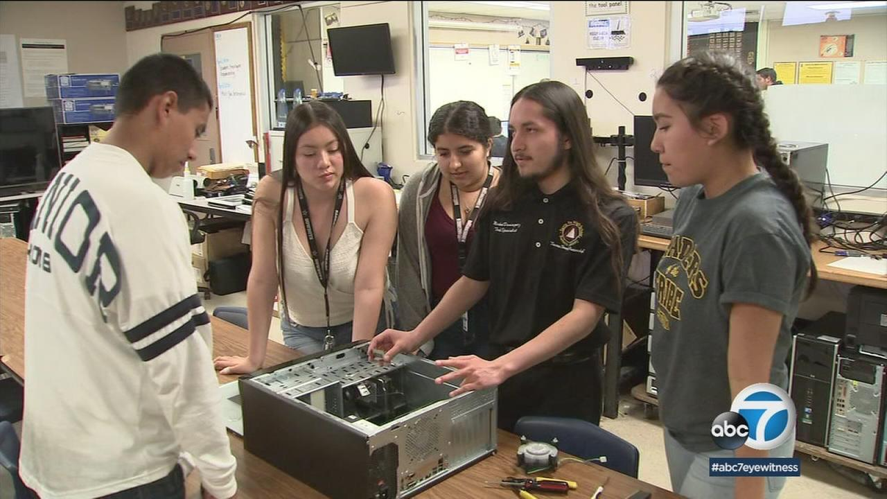 Michael Dominguez is shown showing other students how to put together and work on a computer tower.