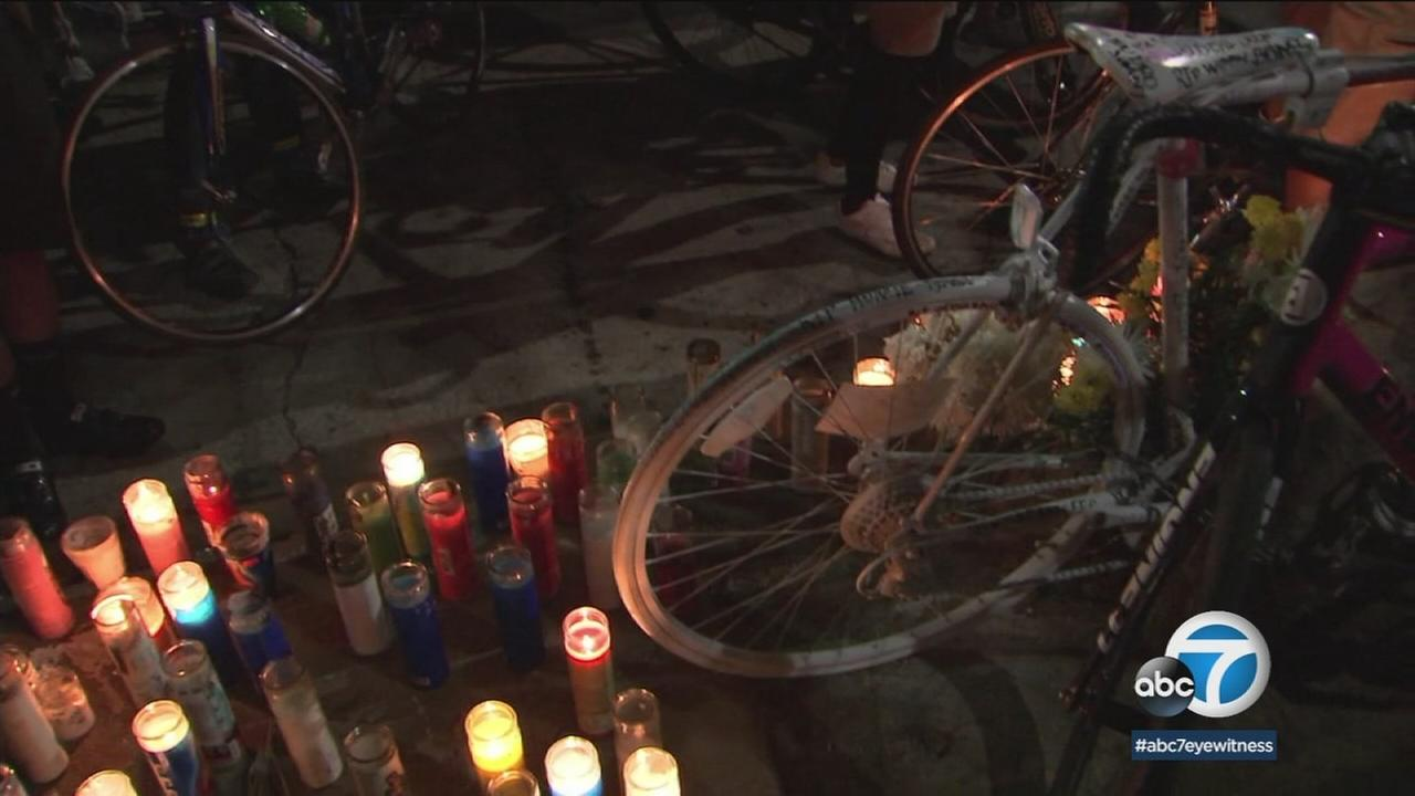A ghost bike and lit candles are shown at a vigil to honor a cyclist who was struck and killed by a hit-and-run driver in South Los Angeles.