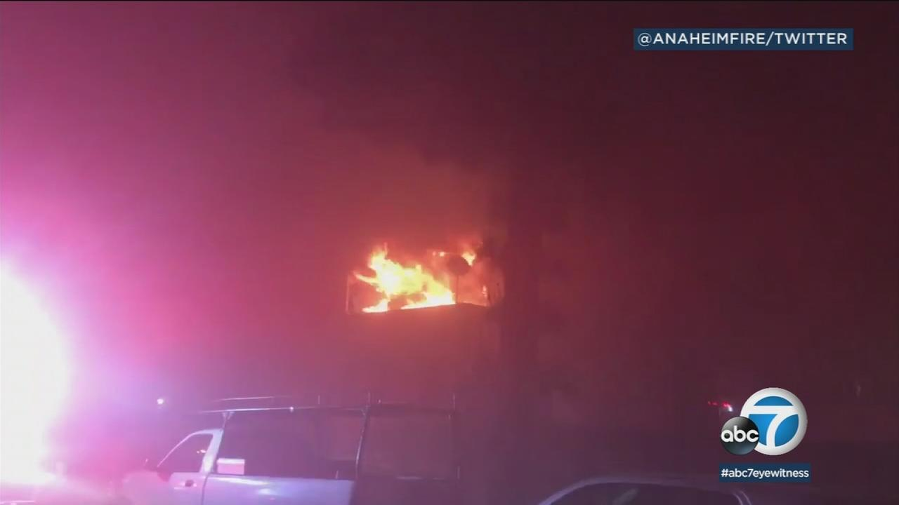 Flames are shown exposing through the roof of an Anaheim apartment complex.