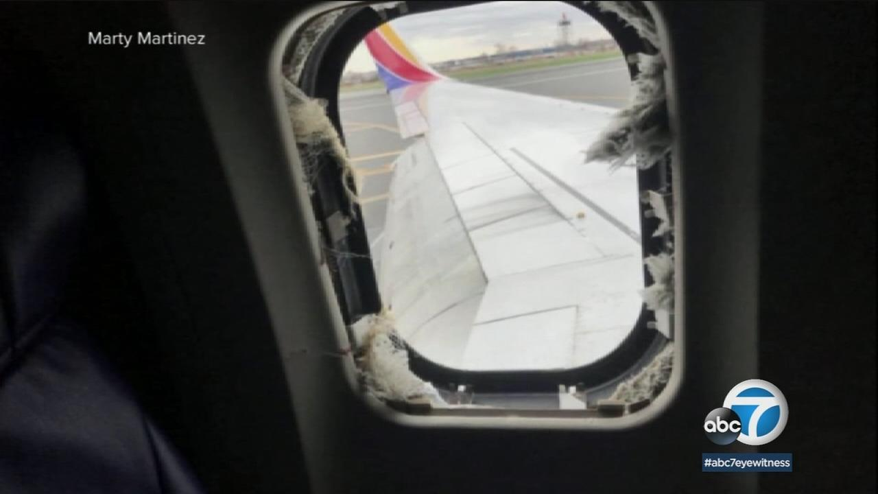 A blown out window on a Southwest Airlines flight that made an emergency landing when an engine exploded is shown in a witness photo.