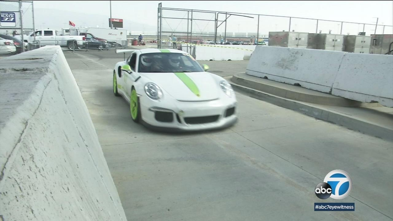 A vintage Porsche on a race track is shown in a photo.
