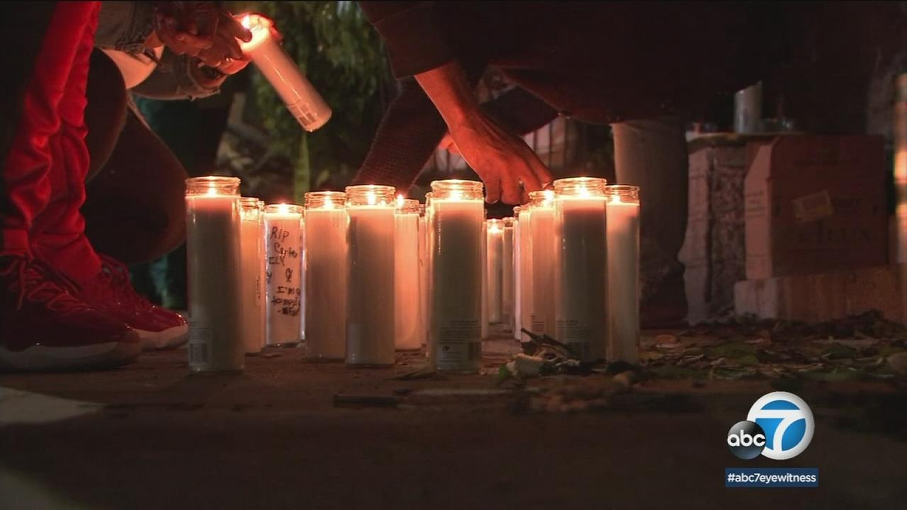 Candles light up the area around a makeshift memorial set up for two friends who were killed in a deadly fire at a Studio City recording studio.