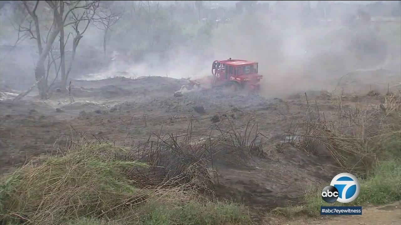 A bulldozer is shown moving charred dirt at the site of a small brush fire in Montebello.