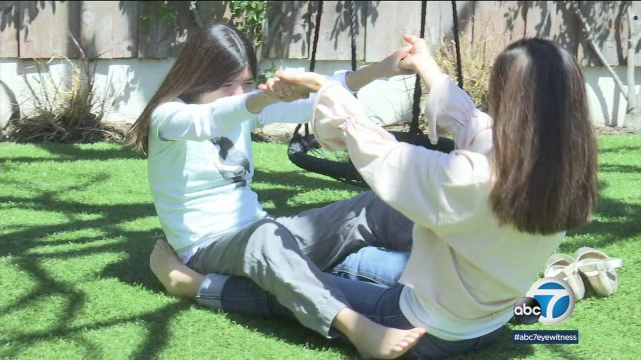 A mother and daughter are shown doing movements therapy during a session.
