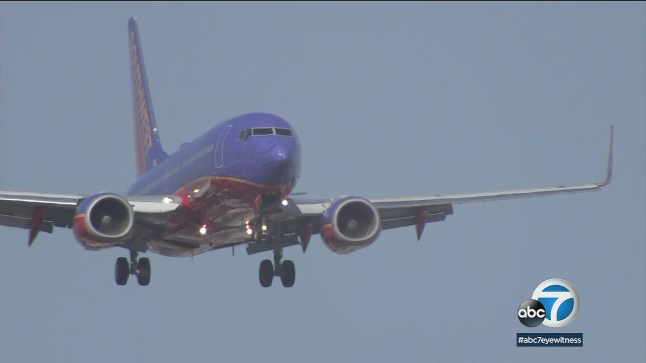 A Southwest plane is shown in a stock photo of planes flying over neighborhoods in Orange County.