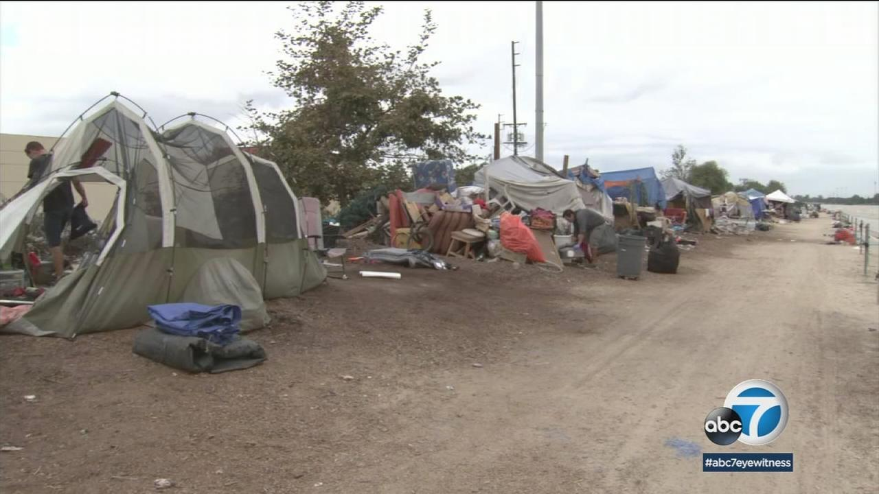 Homeless encampments are shown in a photo.