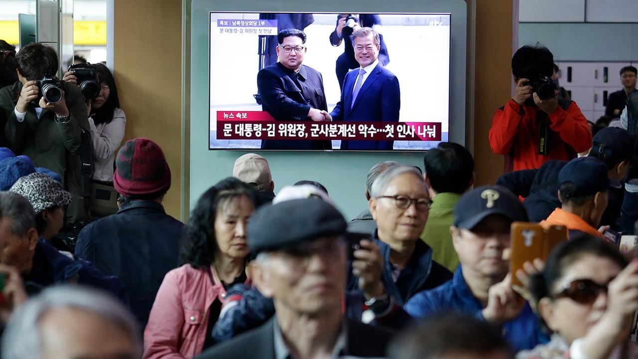 People watch a TV screen showing the live broadcast of South Korean President Moon Jae-in, top right, meets with North Korean leader Kim Jong Un at the border village of Panmunjom.