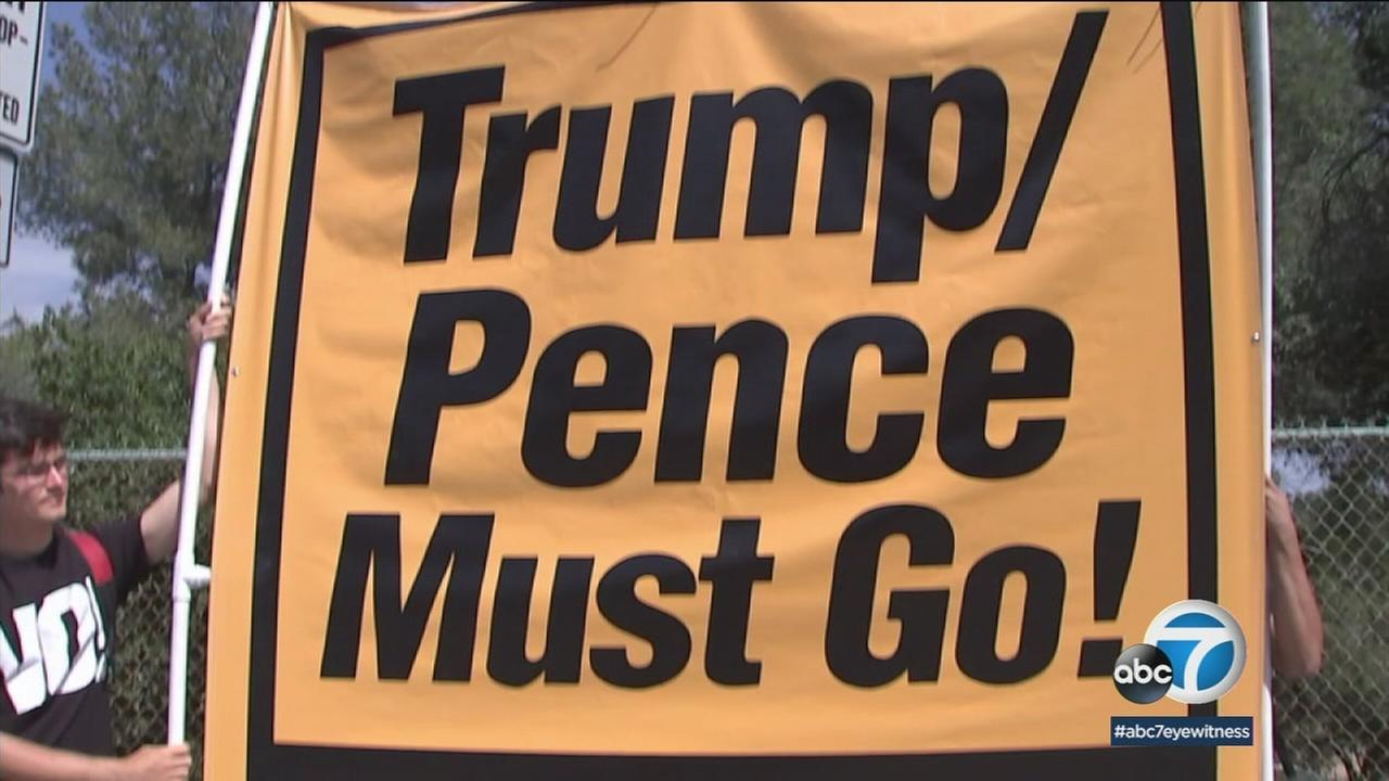 Protesters held up a sign as Vice President Mike Pence visited JPL in Pasadena.
