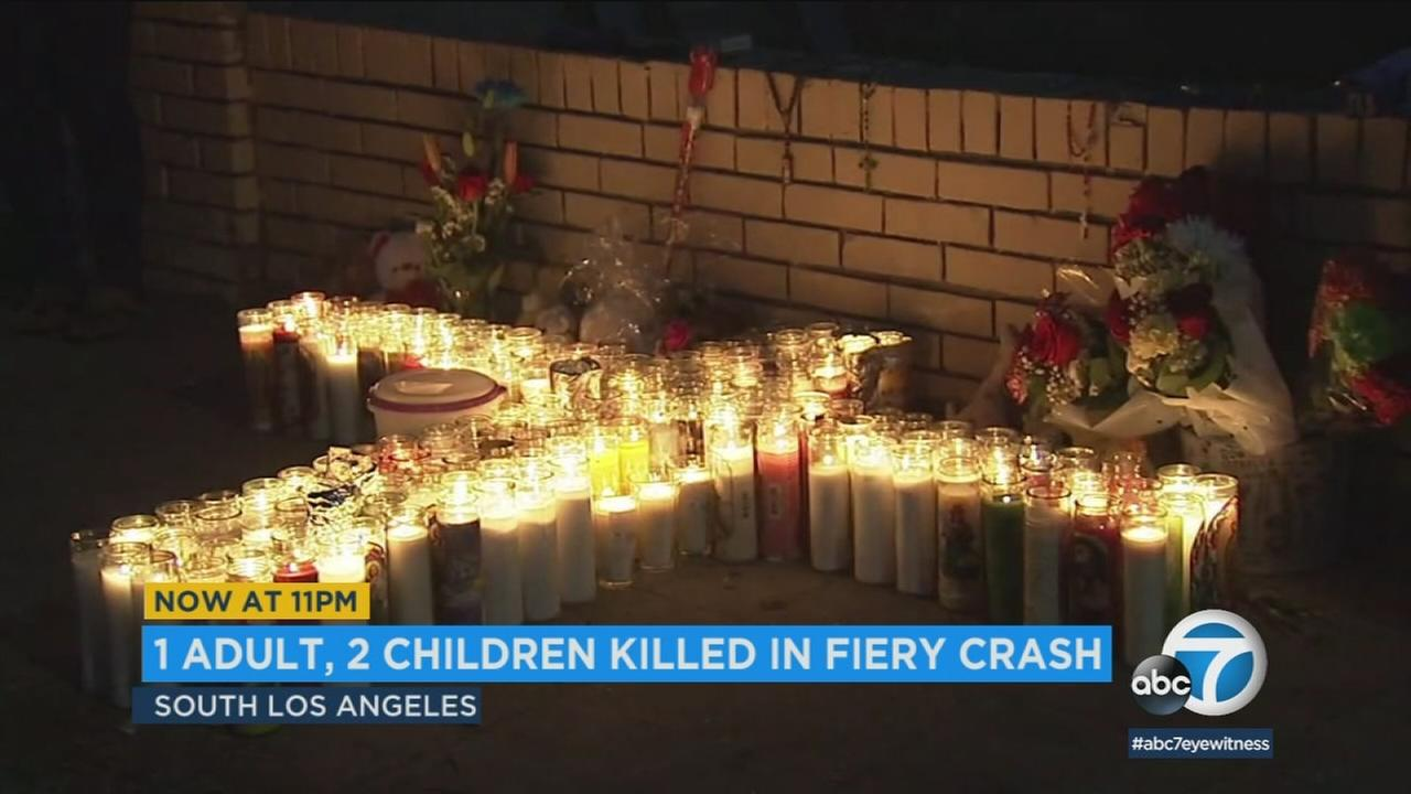 A memorial is growing at the site where a man and two children were killed in a fiery crash in South Los Angeles.