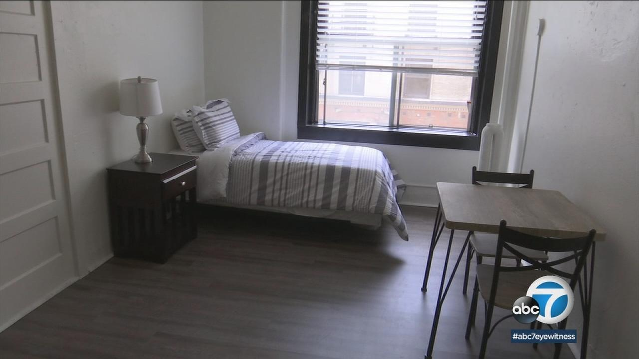 A hotel room repurposed for affordable housing for the homeless is shown in a photo.