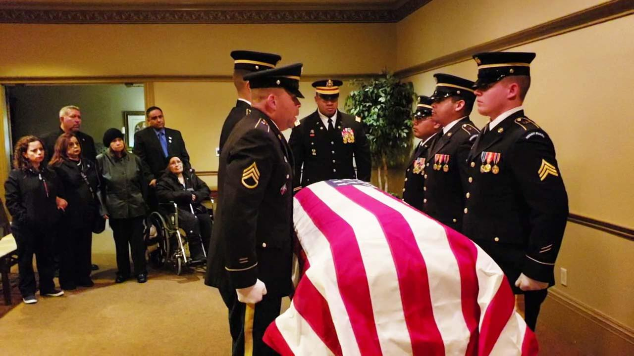 Cpl. Albert Quinteros family members gather around his flag-draped casket.