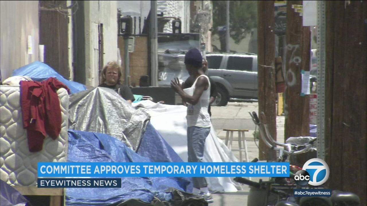 Homeless people at an encampment in downtown Los Angeles are shown.