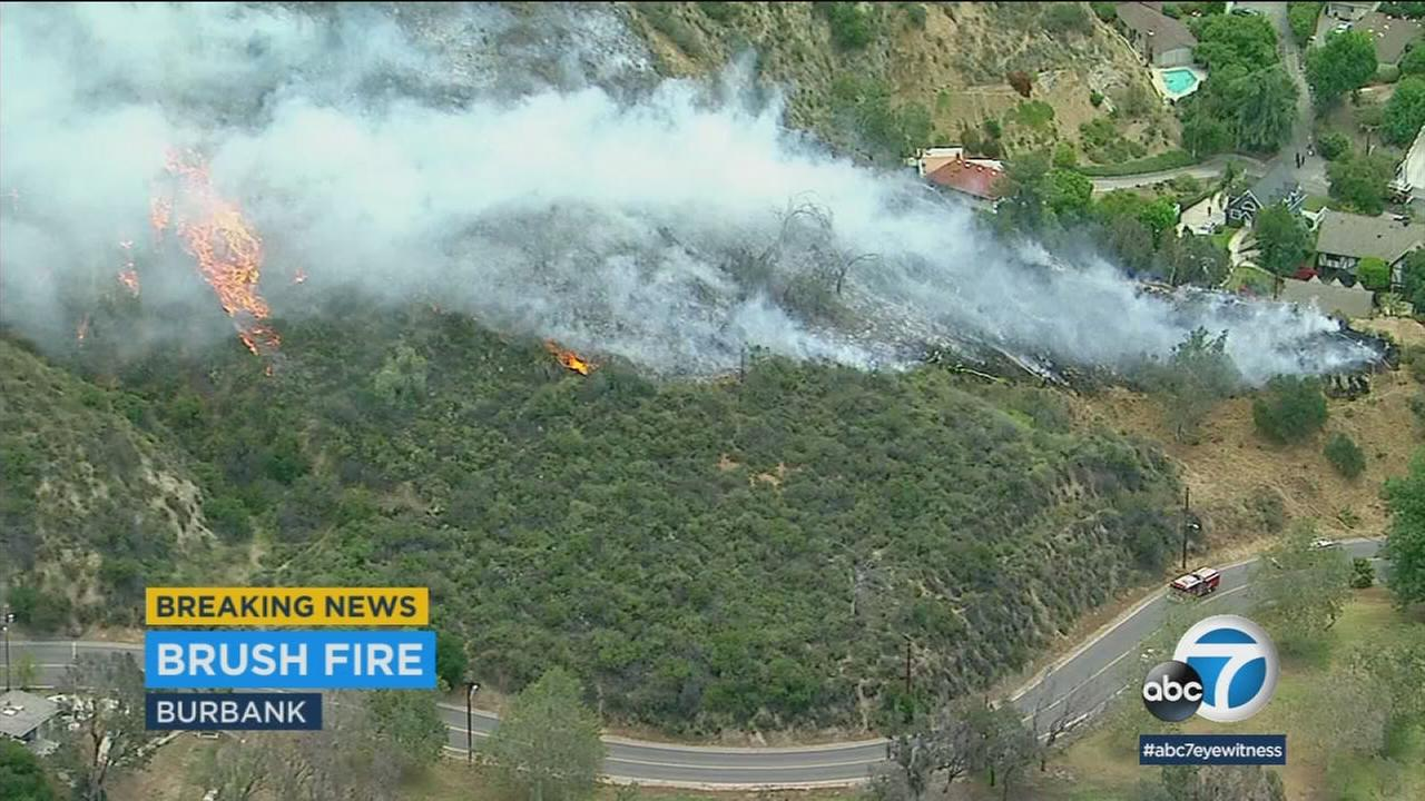 A brush fire in Burbank is shown burning through vegetation.