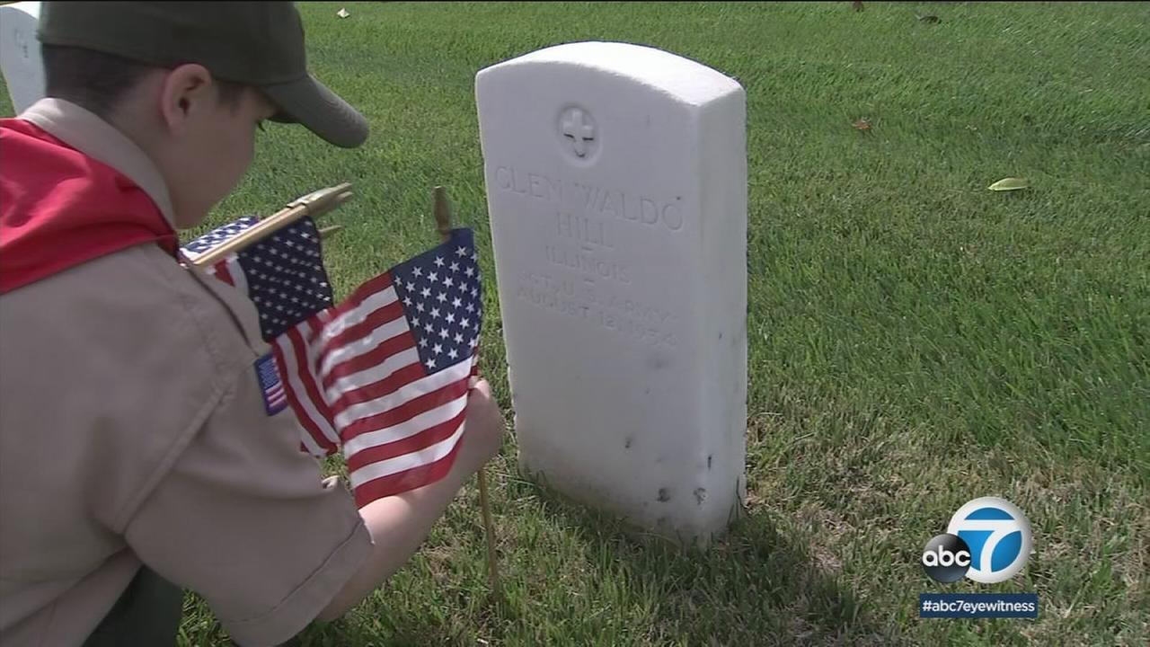 A Boy Scout places a flag at a veterans grave as part of a Memorial Day effort.