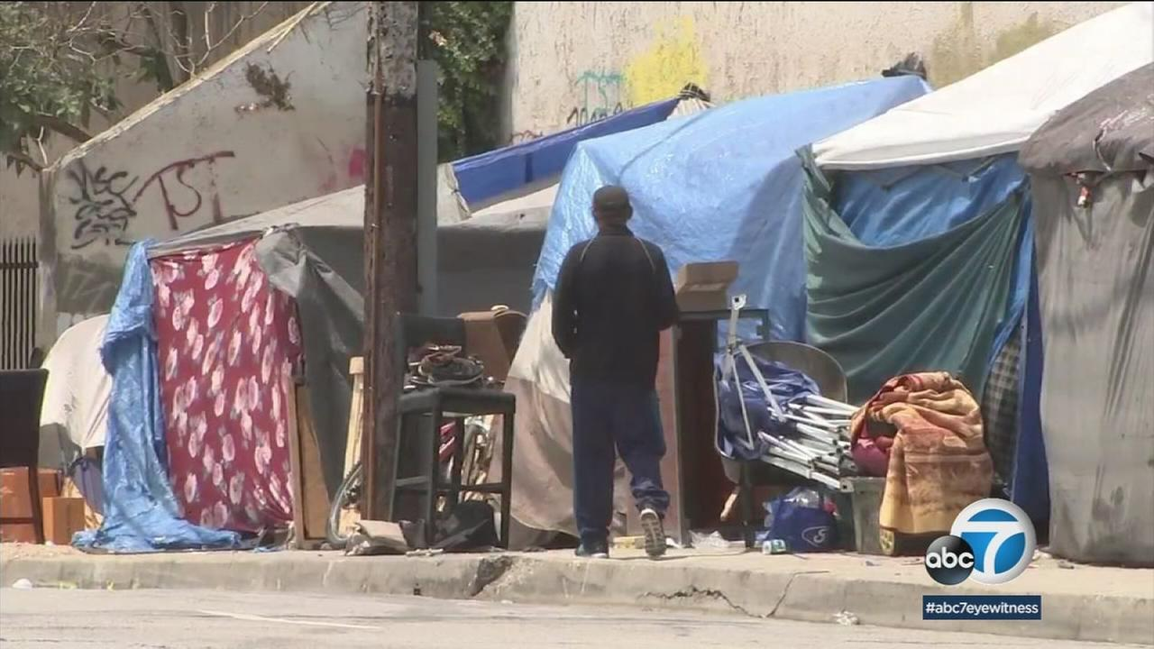 An undated photo of a man near homeless tents in Los Angeles.