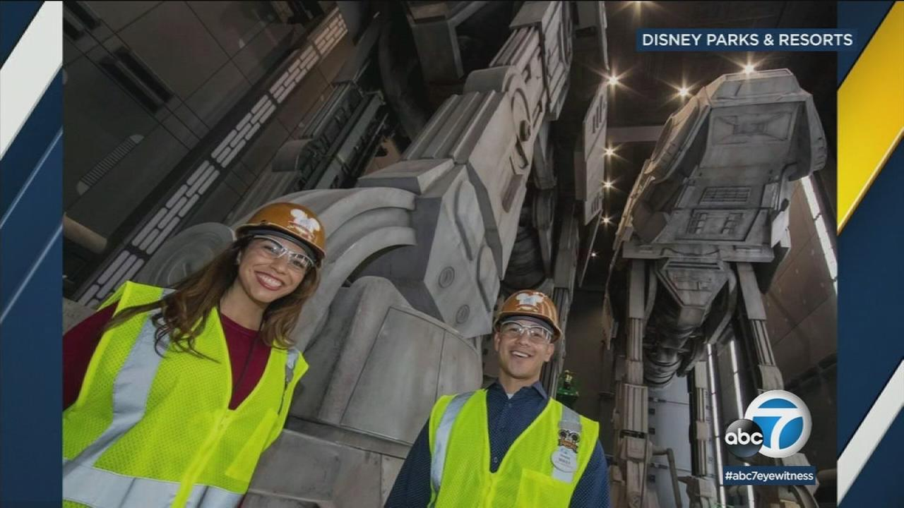 Two Disneyland Ambassadors stand near the massive AT-ATs that are part of the new Star Wars: Galaxys Edge area of the park.