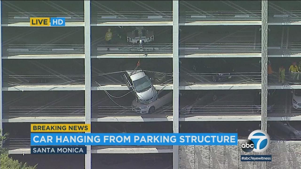 A vehicle hangs off of the fourth floor of a parking structure in Santa Monica on Monday, June 11, 2018.