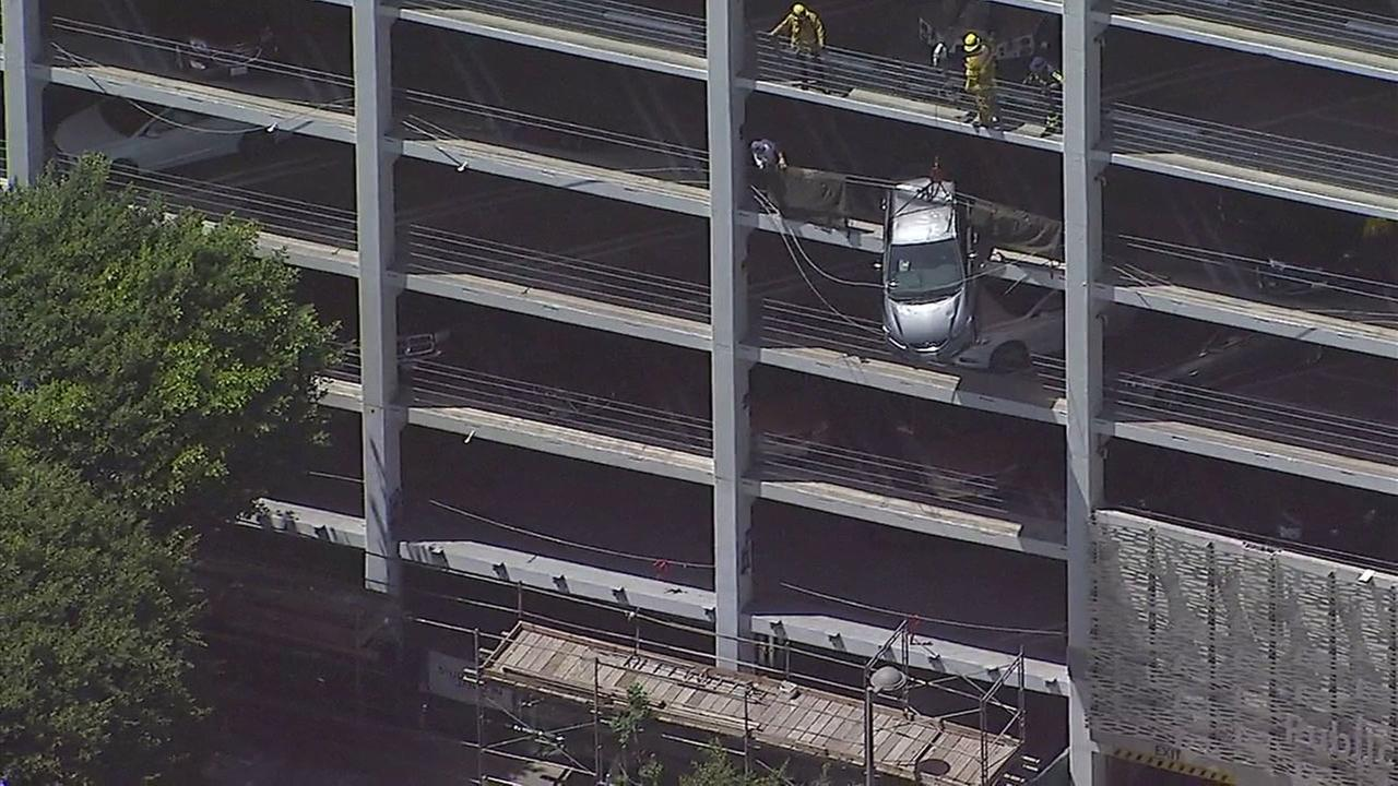 A vehicle dangled from the fifth floor of a parking structure in Santa Monica on Monday, June 11, 2018.