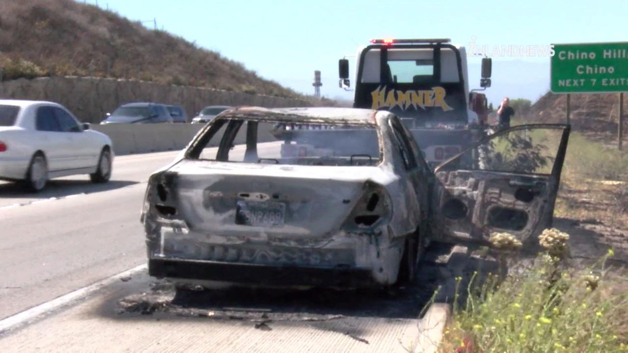 A charred car that sparked a brush fire along the 71 Freeway south of Chino on Tuesday, June 12, 2018.