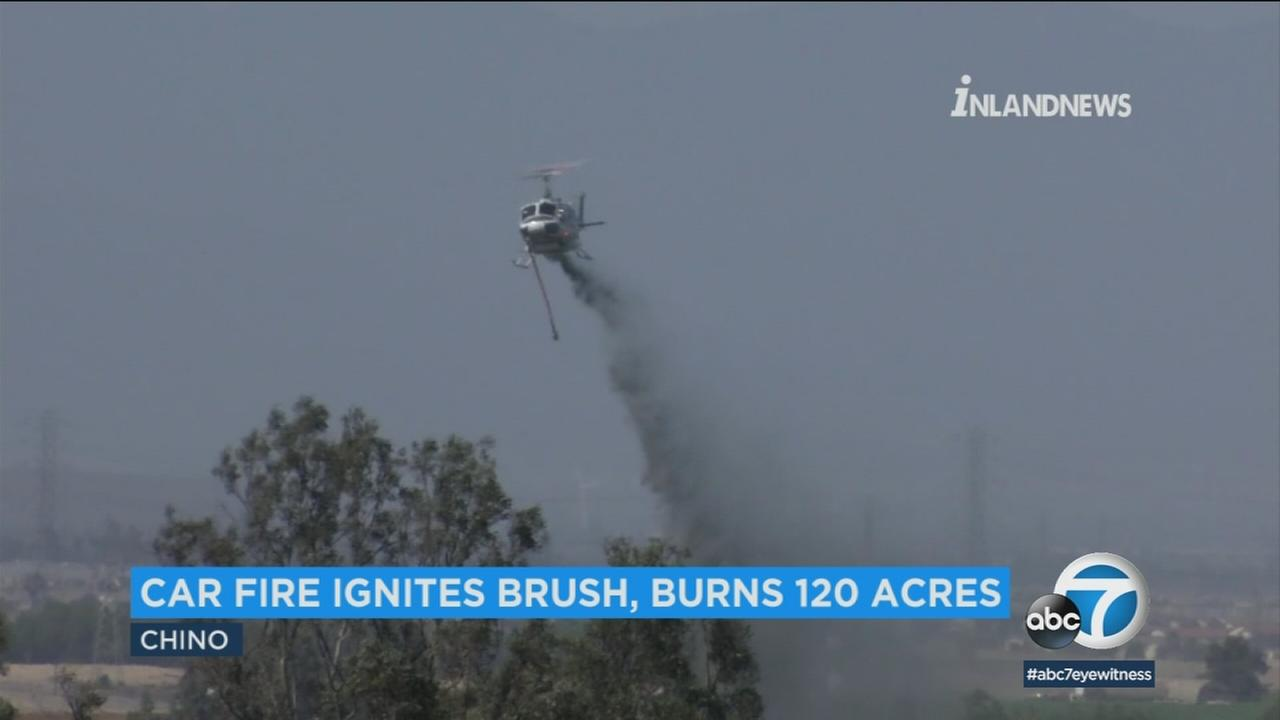 A helicopter drops water over a fire that was started by a car fire in Chino.