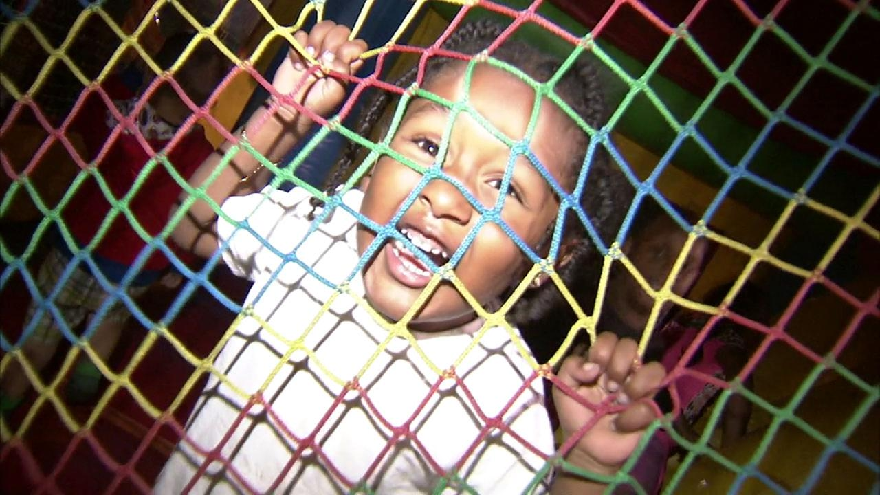 A child acts silly as she plays in a bouncy house during a Parks After Dark event.