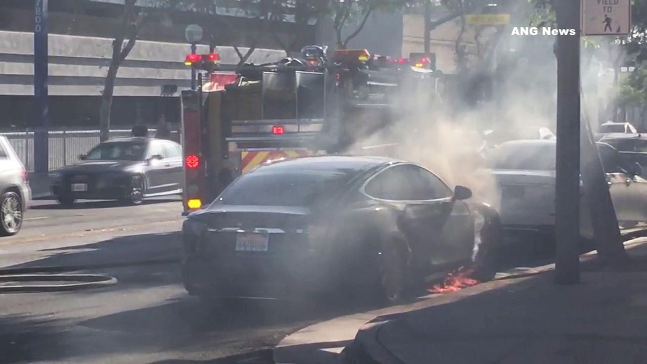 Fire investigators are looking into what caused a Tesla to burst into flames on a West Hollywood street.