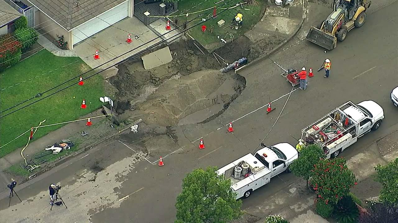 Crew work on repairing a road in Downey, where a car crash resulted in a large sinkhole.