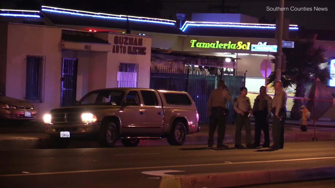 Law enforcement officials are seen in Lynwood, where a man was found fatally shot inside a car.