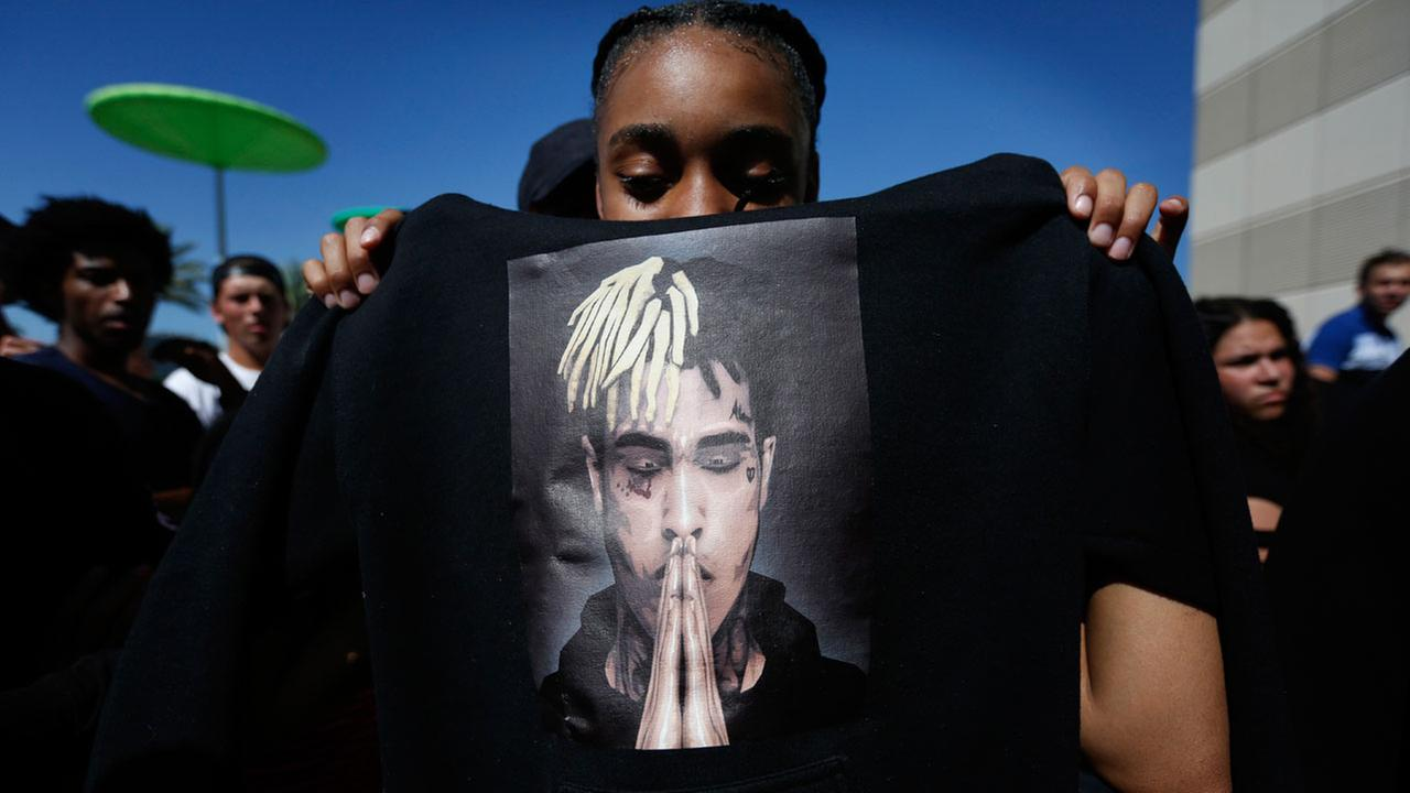 Anneyah Lawson, 14, of St. Petersburg, Fla., holds up a sweatshirt with an image of slain rapper XXXTentacion, before his memorial on Wednesday, June 27, 2018, in Sunrise, Fla.