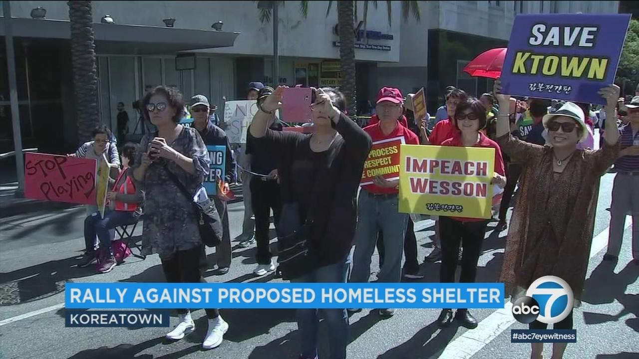 People are shown at a rally that is against a temporary homeless shelter that would be in Koreatown.