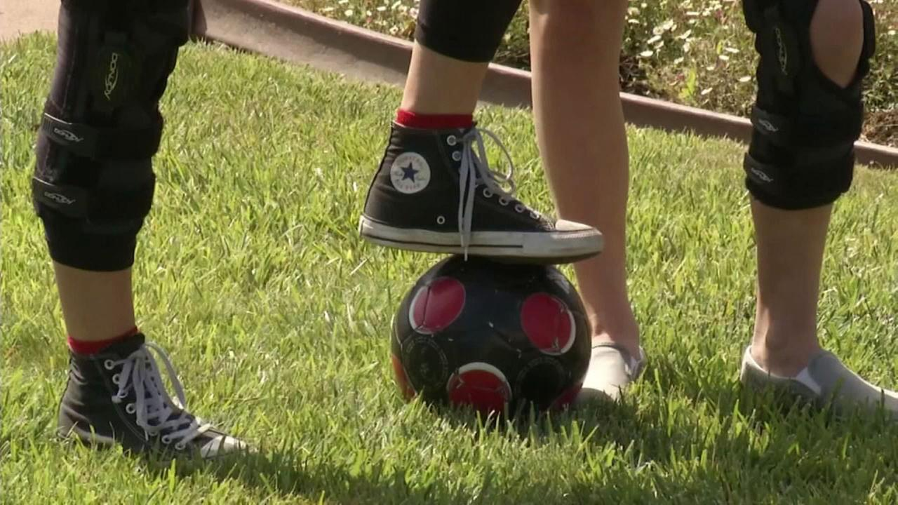 Two siblings with ACL are shown with a soccer ball and leg braces.