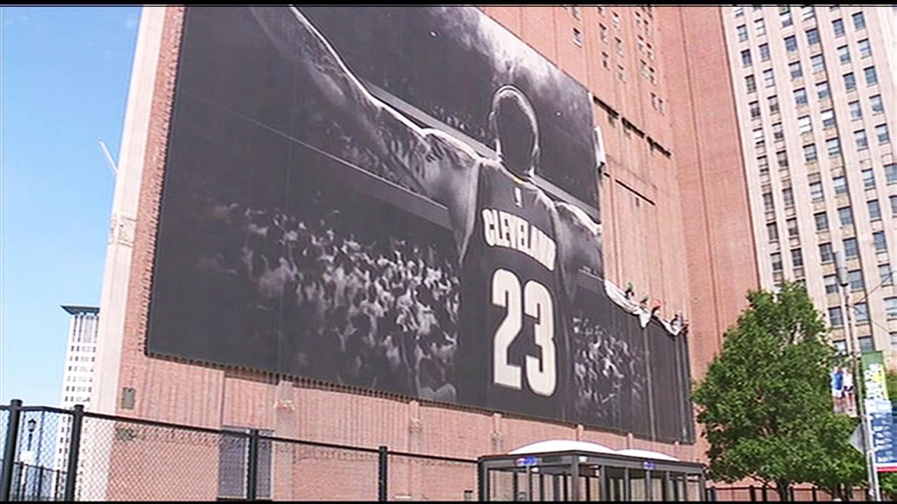 An iconic banner of LeBron James comes down from a building in downtown Cleveland, Ohio, on Tuesday, July 3, 2018.