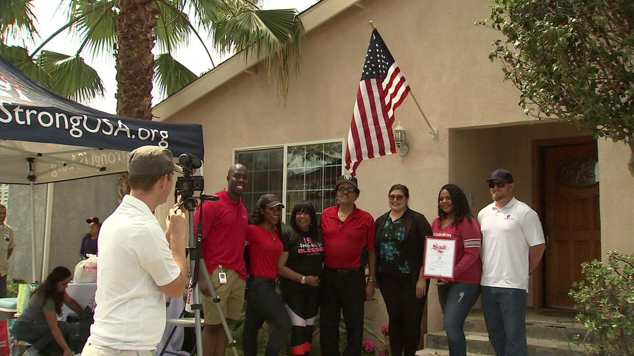 Edward Horne is shown taking photos with his family and volunteers who helped patch up his Inglewood home.