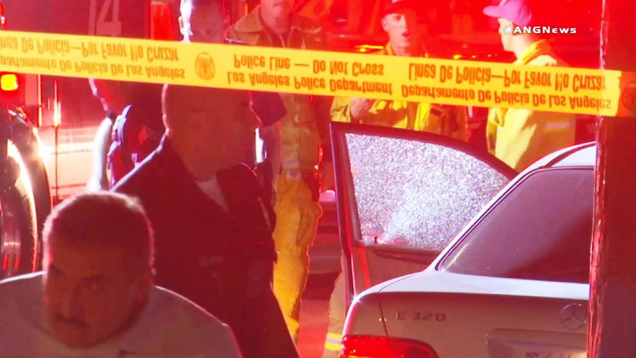 Law enforcement officials investigate the scene of an apparent road rage shooting near South Los Angeles.