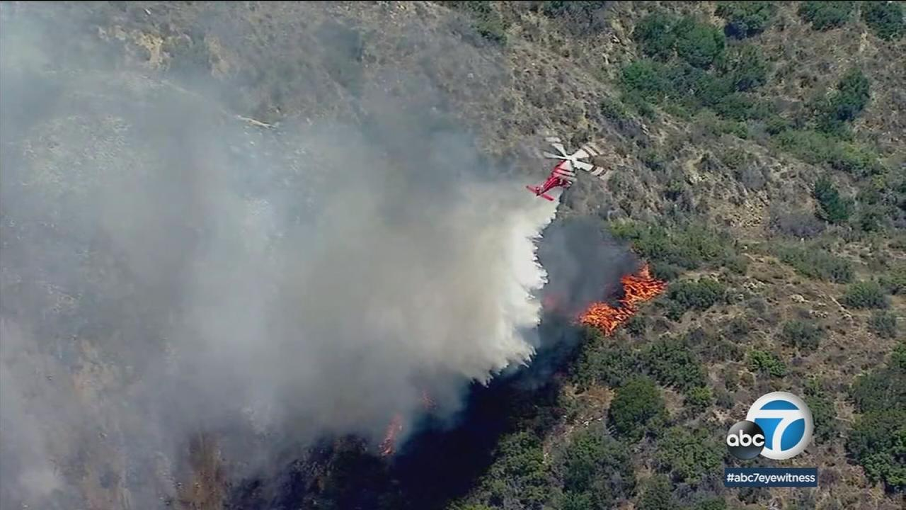A helicopter dropped water on a fire in the Burbank hills on Saturday, July 7, 2018.